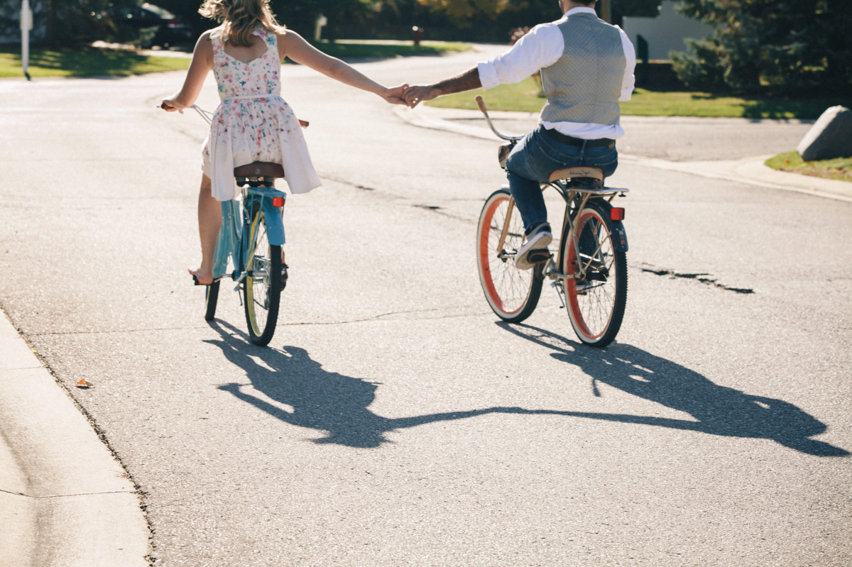 A couple rides bikes during their engagement session in Howell, Michigan